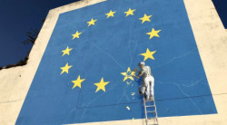 Banksy's mural of a workman chiselling at a star in the European Union flag on the wall of a building in Dover, England